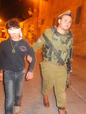 Armed Israeli soldier leads blindfolded boy