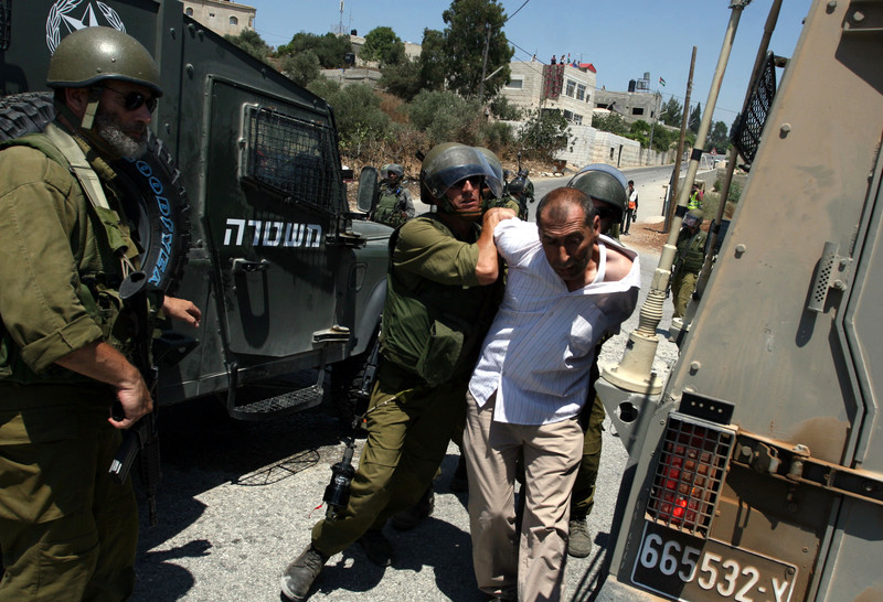 Armed Israeli soldiers arrest unarmed Palestinian man