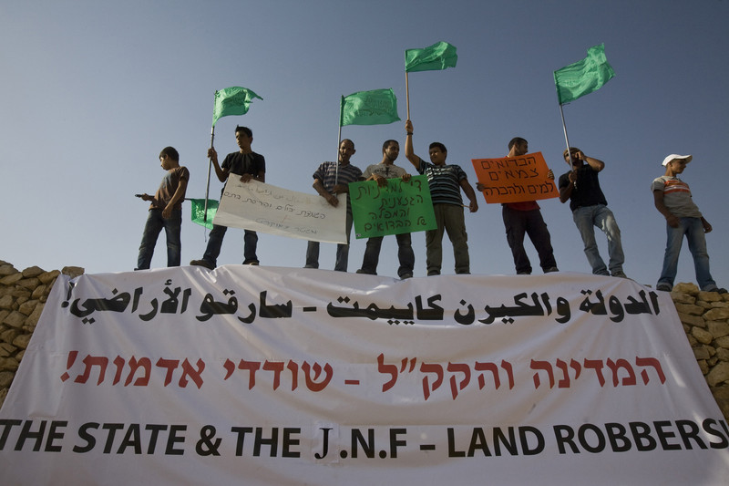 "Men carrying signs and flags stand above banner reading ""State & the JNF - Land Robbers"" in Arabic, Hebrew and English"