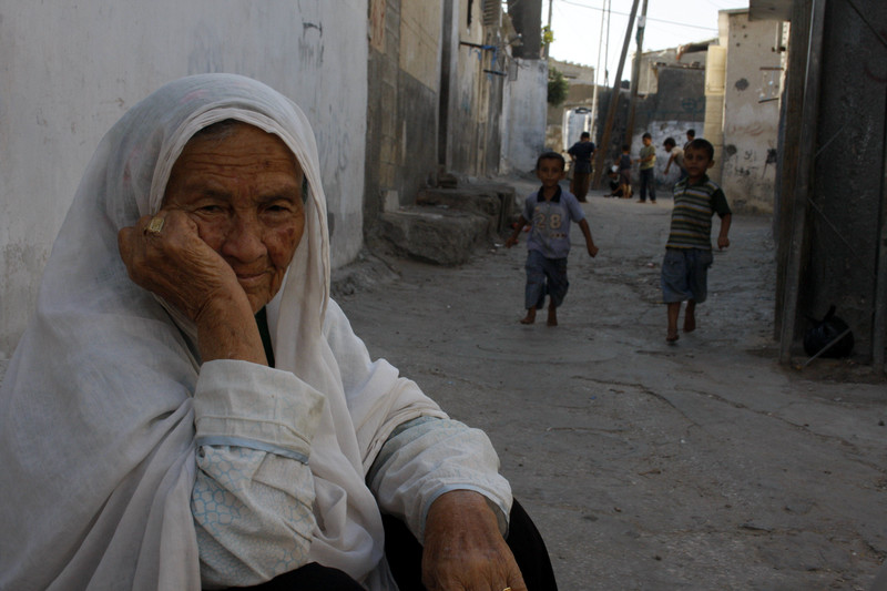 Elderly woman sits in refugee camp