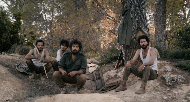 Men in military clothes sit in forest camp