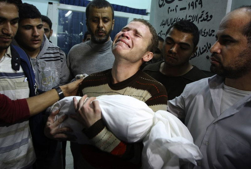 Anguished man holds body of child wrapped in white sheet