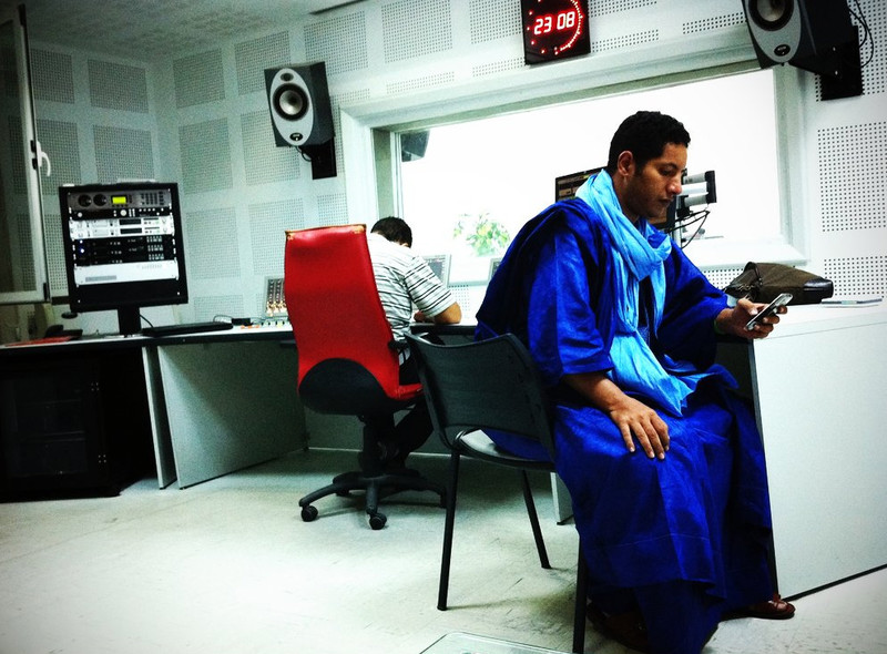 Man wearing blue robe looks at his phone in a radio station suite