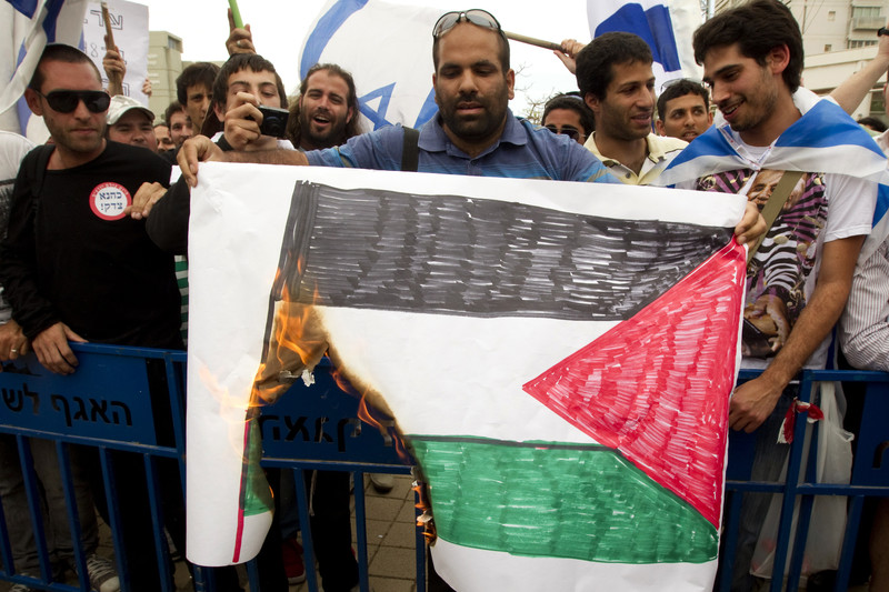 Man burns poster of Palestinian flag with people waving Israeli flags in background