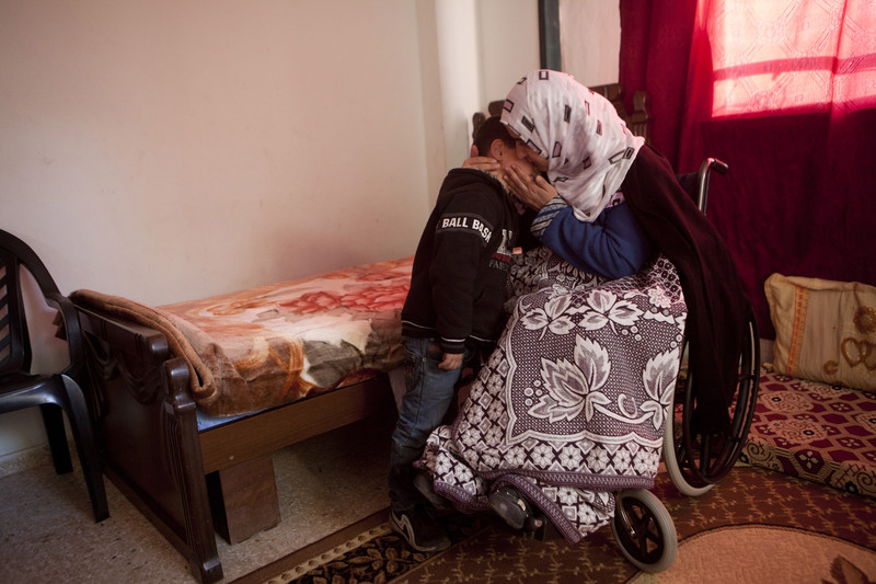 Women embraces son in their residence