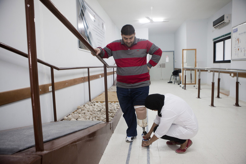 Woman assists man being fitted with prosthetic leg