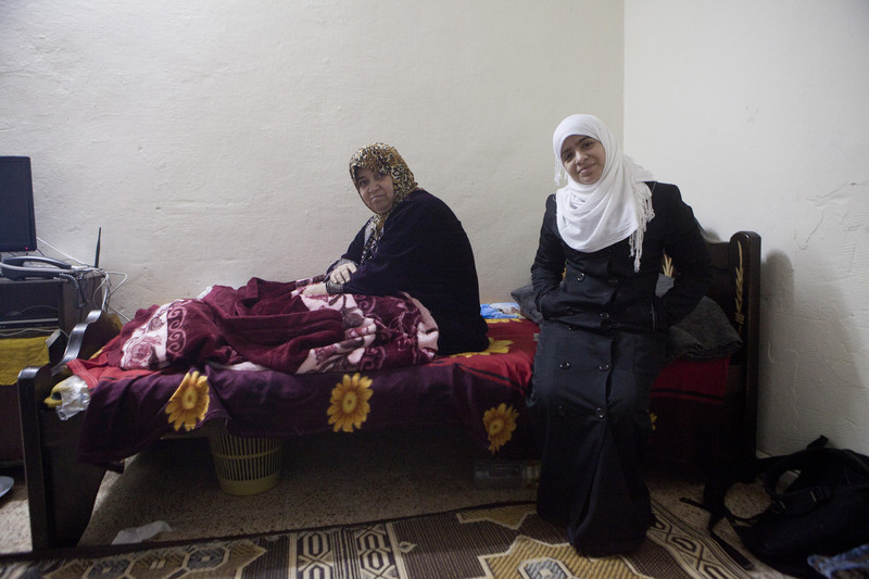 Older woman sitting on bed and and younger woman standing in front of bed smile at camera
