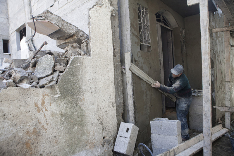 Laborer covered in dust holds up board