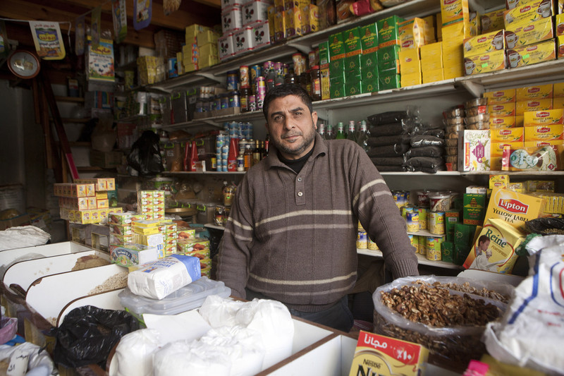 Man stands surrounded by grocery goods