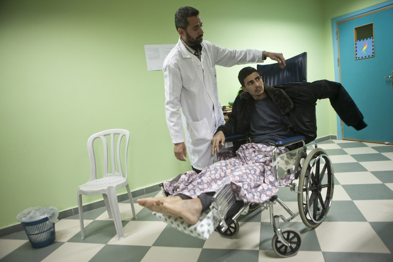 Medical aide stands next to man using wheelchair