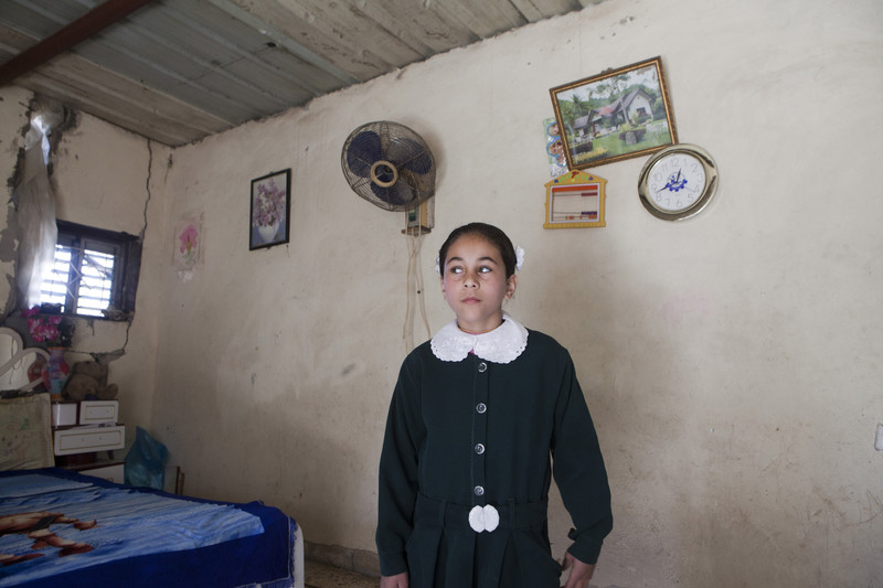 Girl stands in modestly decorated room