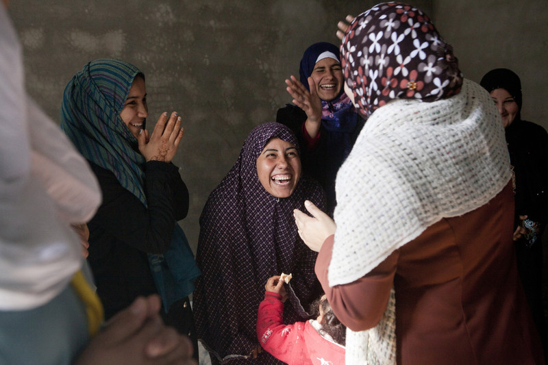 Women laugh and clap together