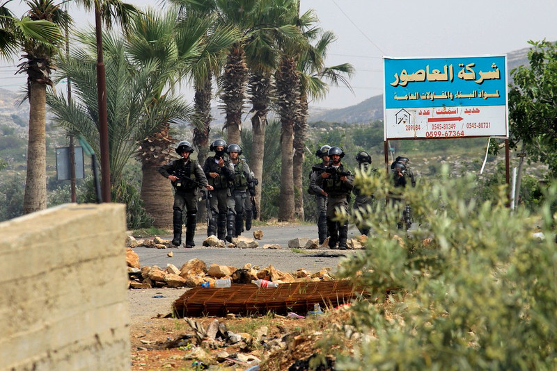 Heavily armed soldiers stand in front of palm trees