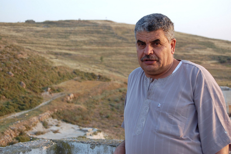 Man stands with Israeli outpost on hill in background