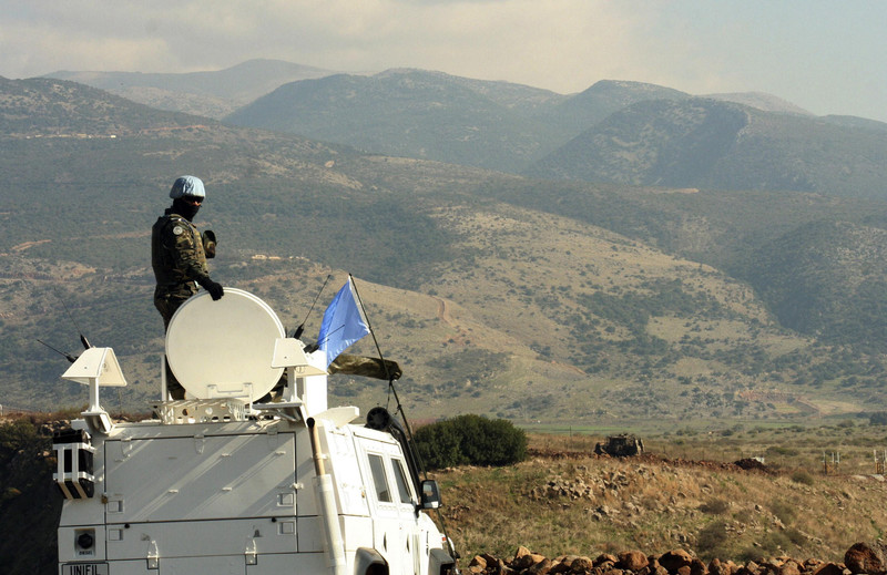 UN soldier atop armored vehicle overlooks Lebanon-Israel border