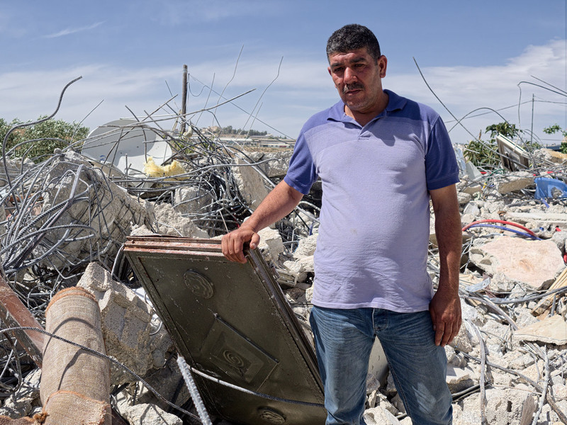 Man holds piece of the rubble of his home, seen in background