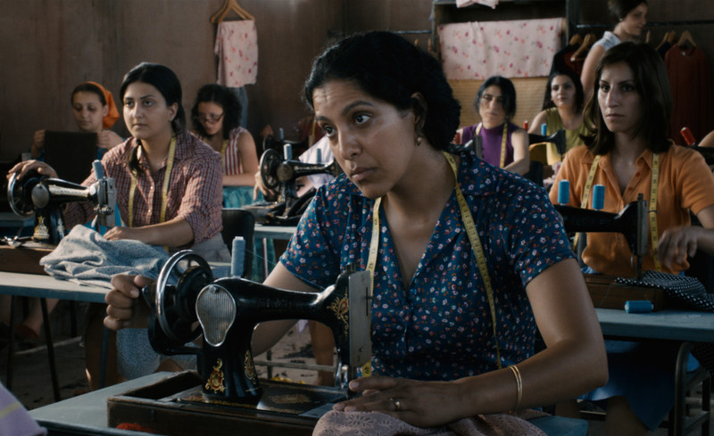 Close up of woman sitting behind sewing machine in room full of seamstresses