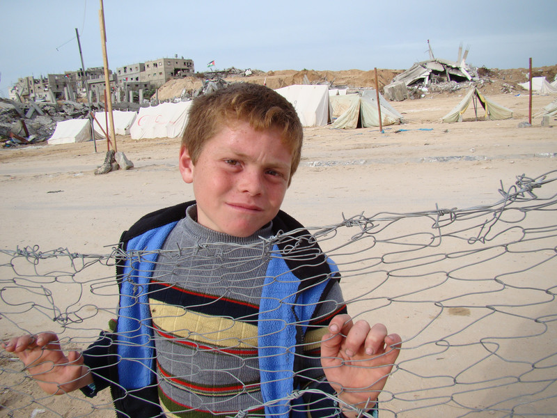 Boy leans against fence with tents and destroyed homes in background