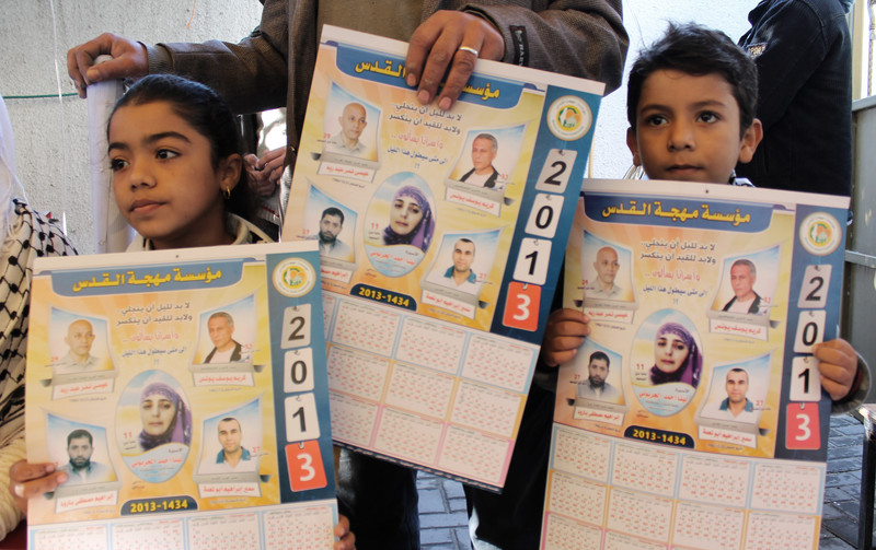 Children hold calendars with photos of political prisoners