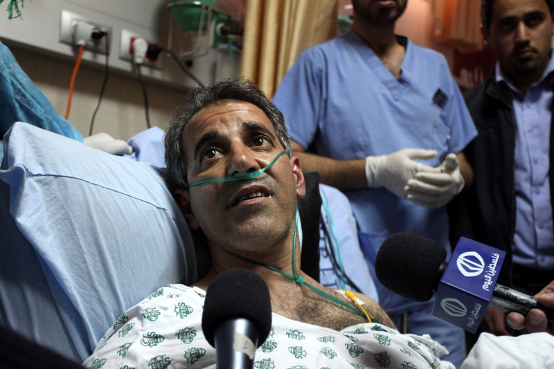 Man on hospital bed surrounded by microphones