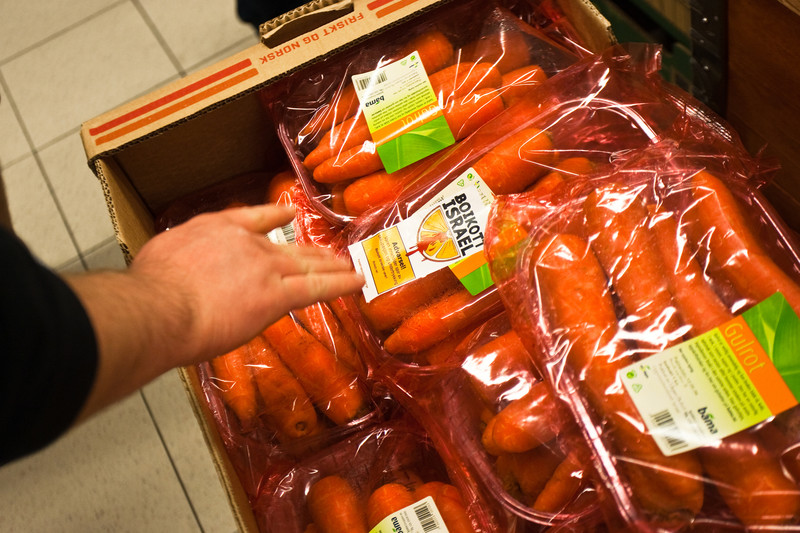 Hand puts Boycott Israel sticker on box of bagged carrots