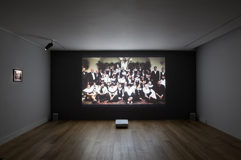 Installation view of projection of posed group of people in masquerade costume