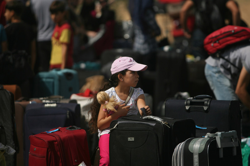 Girl holding doll sits amidst suitcases