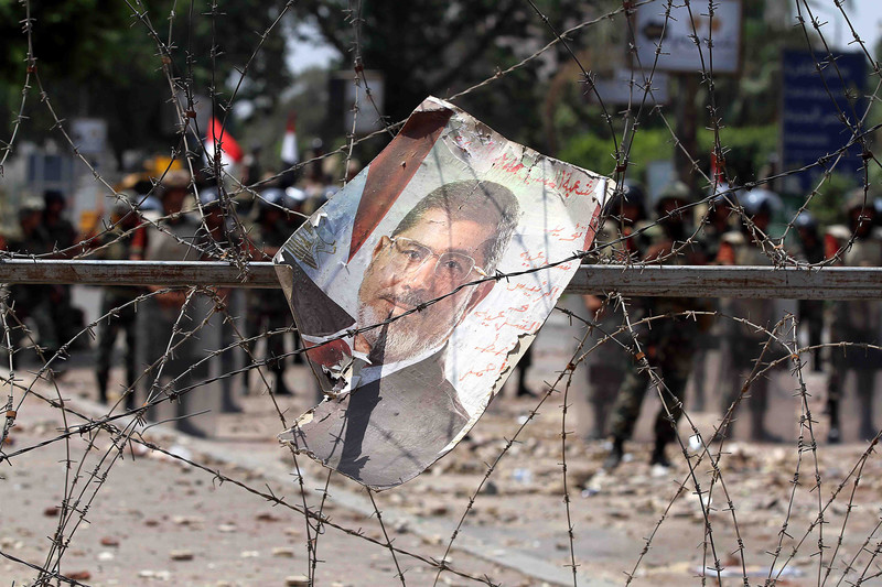A poster of Mohammed Morsi entangled in barbed wire, with soldiers in background