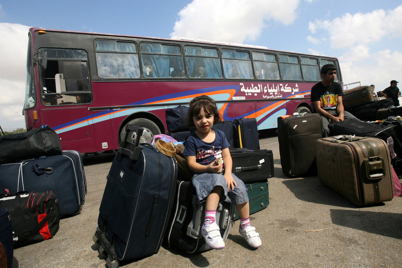 Girl sits amid suitcases in front of bus