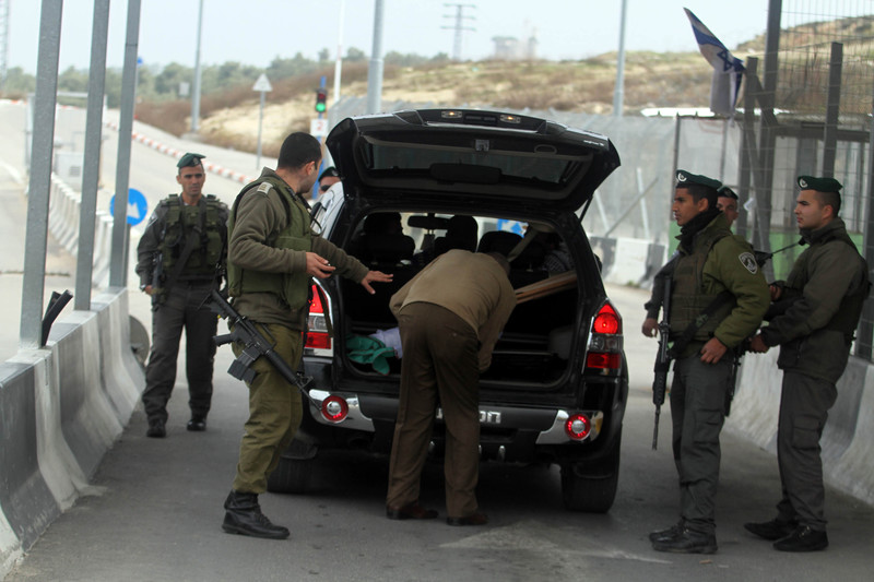 Man opens boot of car as soldiers look on