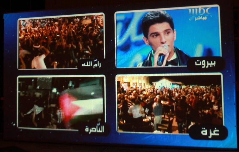 Photograph of projection of split-screen footage of people celebrating