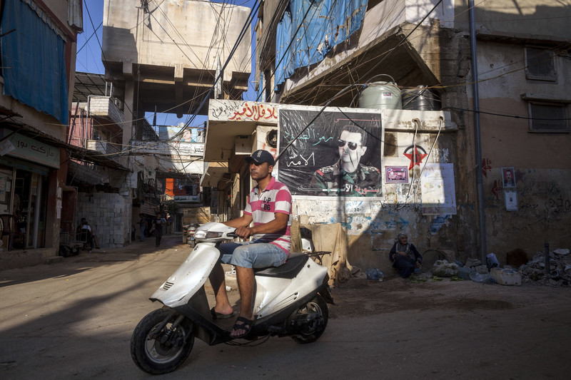 Scene shows youth on scooter riding past wall covered with poster and graffiti
