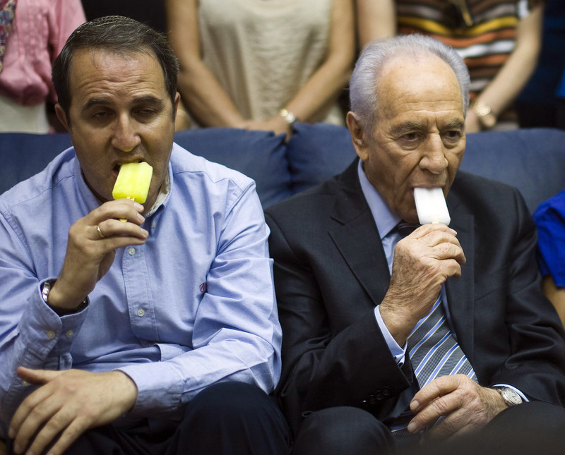 Two men, including Israeli president Shimon Peres, appear unhappy while eating ice cream
