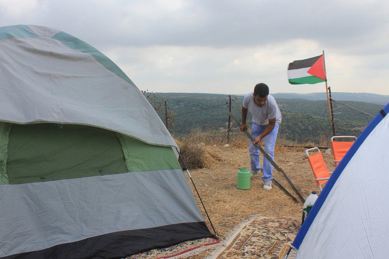 Man picks up bar amid tents with Palestine flag and landscape in background