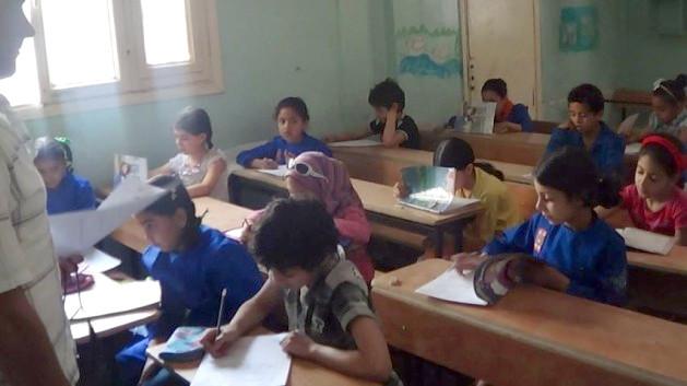 Children sit at school desks