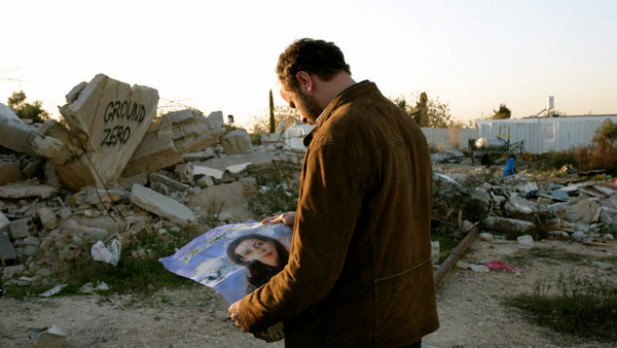 Man looks at the poster he is holding of woman, with rubble in background
