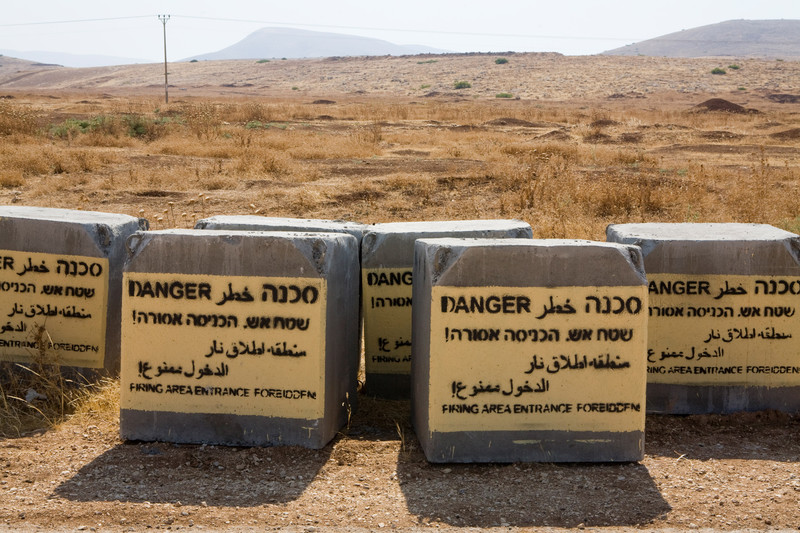 Concrete blocks spraypainted with text warning of live fire military zone