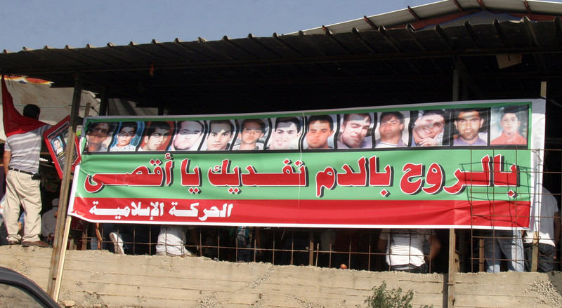 Arabic-language banner features the portraits of 13 males shot by Israeli police