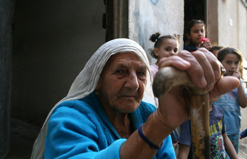 Elderly woman holding cane sits in front of children in alleyway