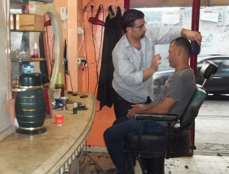 Young man grooms another man sitting in barber shop chair
