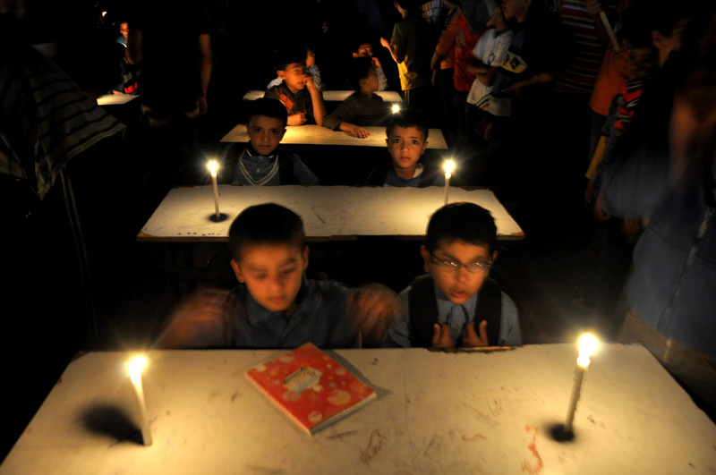 Boys sit at school desks in room lit with candles