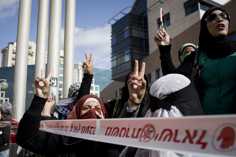 Women make victory sign with their hands during protest
