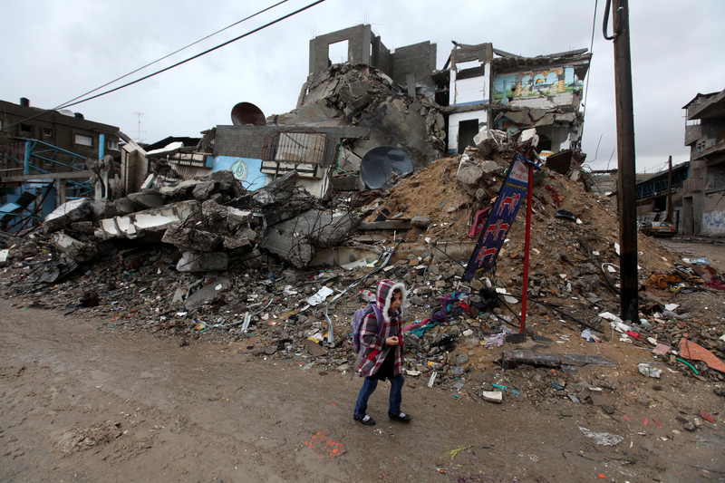 Girl walks in front of bombed-out building
