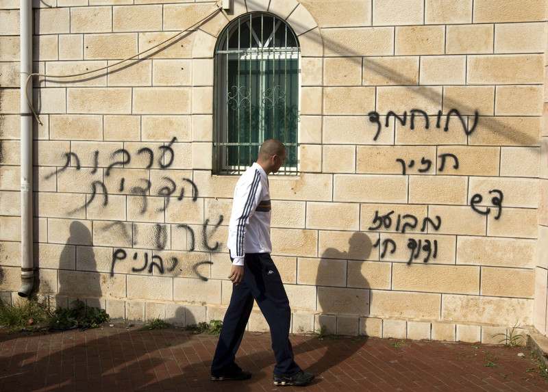 Man walks in front of stone wall spray painted with Hebrew graffiti