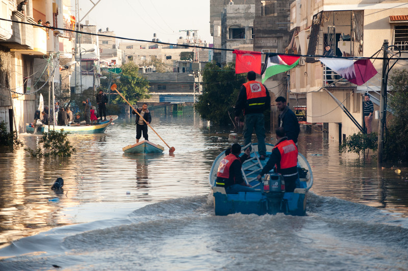 Men in small boats paddle through flooded urban area