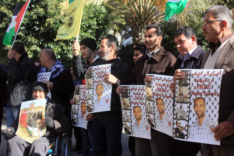 Men hold posters of Palestinian prisoner