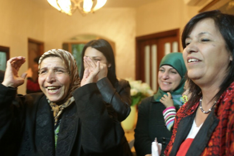 Women of different generations tearfully smile and gesture with their hands