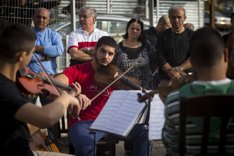 Young man plays the viola as others look on