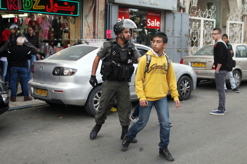 An Israeli soldier arrests a Palestinian child.
