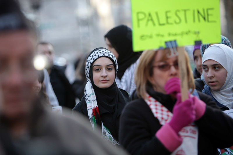 Young woman looks at camera during Palestine solidarity rally